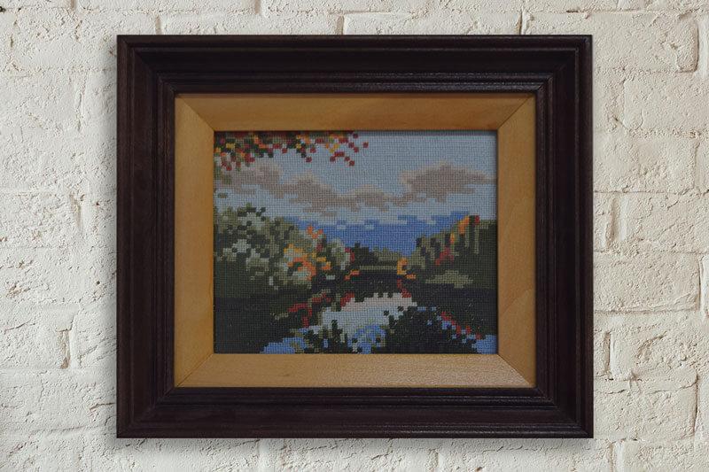 Гоблен планински пейзаж рамкиран в правоъгълна рамка от тъмно дърво със светла подрамка