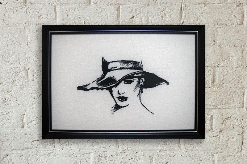 Гоблен момиче с шапка рамкиран в правоъгълна черна рамка от дърво със сребърна ивица